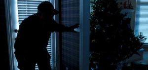 burglar in house next to Christmas tree