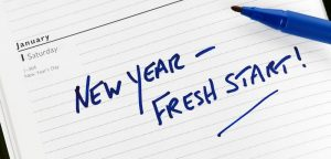 """new year - fresh start"" written on notepad"