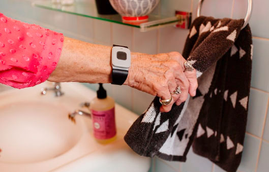 arm of an elderly woman wearing a nurse call system on her wrist as she reaches for hand towel