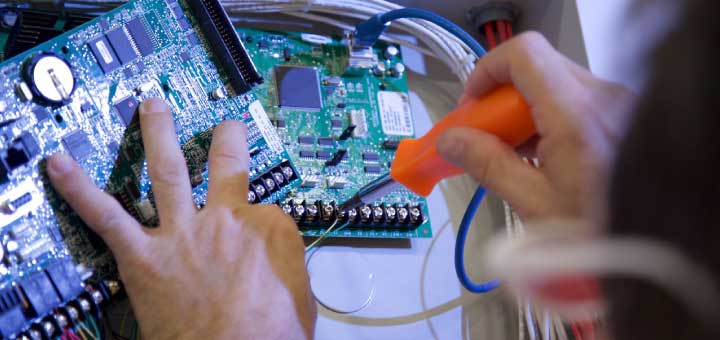 man repairing security system control board
