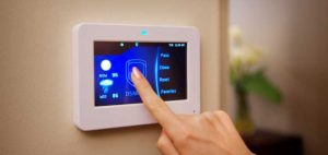 woman using security system touchscreen panel
